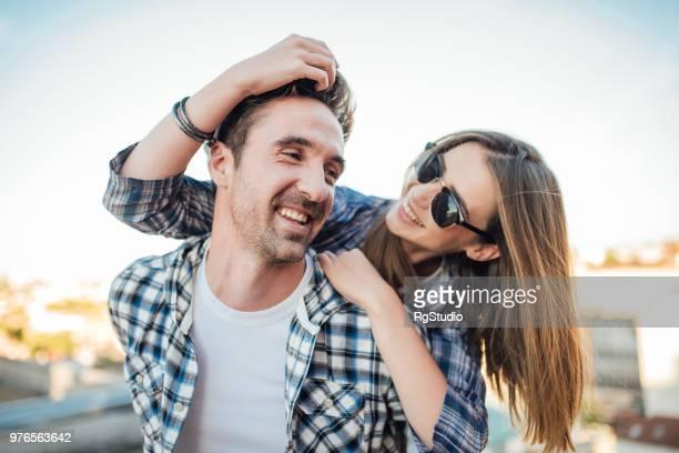 mulher com óculos de sol tocar no cabelo do homem bonito na parte superior do telhado - mão no cabelo - fotografias e filmes do acervo
