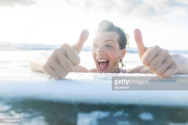 Woman with surfboard in sea giving thumbs up, Nosara, Guanacaste Province, Costa Rica