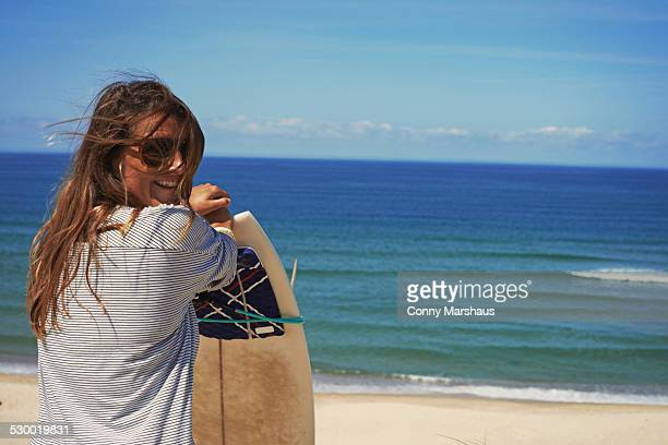 woman with surfboard on beach, lacanau, france - aquitaine stock photos and pictures