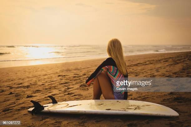 woman with surfboard relaxing at beach during sunset - blond frauen strand stock-fotos und bilder