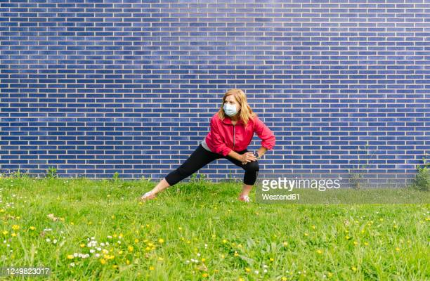 woman with surgical mask stretching her leg on meadow - face guard sport stock pictures, royalty-free photos & images