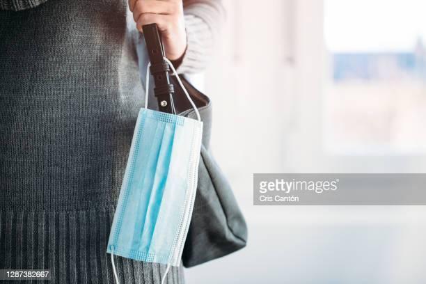 woman with surgical mask tied to her handbag - cris cantón photography fotografías e imágenes de stock
