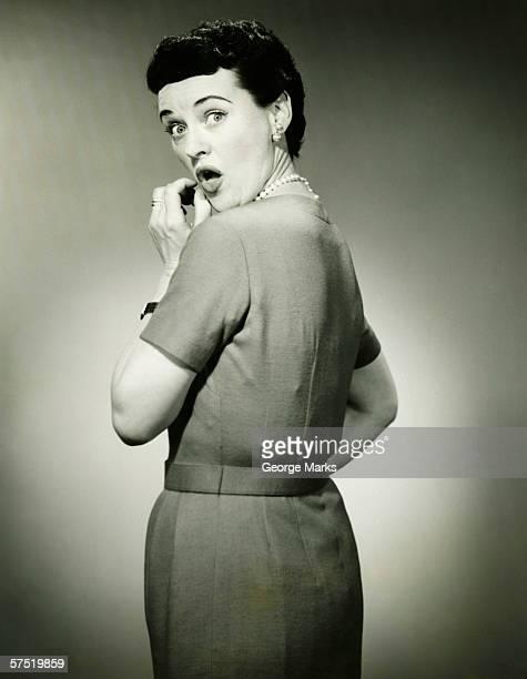 Woman with surprised look in studio, (B&W),  portrait