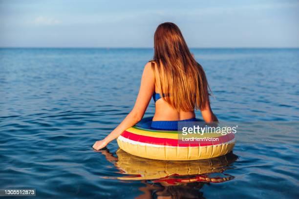 donna con anello da bagno sulla spiaggia - henri coste foto e immagini stock