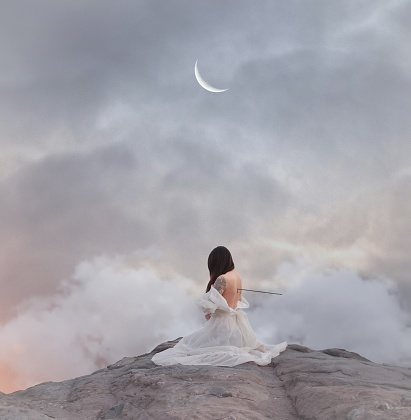 Woman With Sword In Back Sitting On Rock Against Sky - gettyimageskorea
