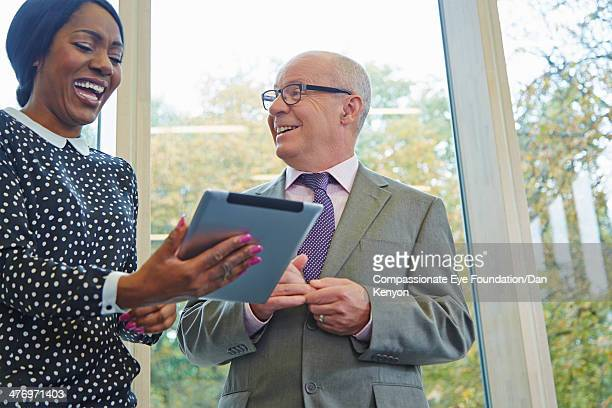 woman with table device laughing with colleague - leanintogether stock pictures, royalty-free photos & images