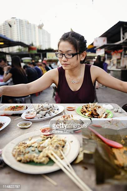 Woman with table of street food, penang