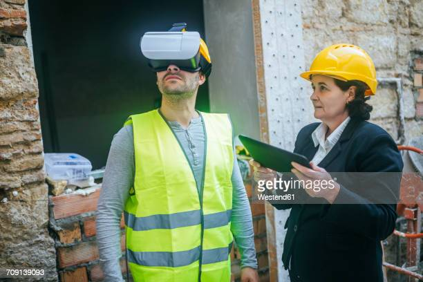Woman with tablet and construction worker with VR glasses on construction site