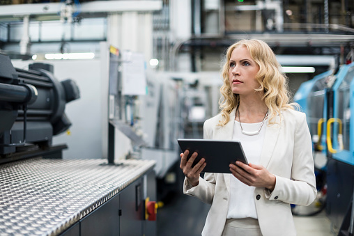 Woman with tablet at machine in factory shop floor looking around - gettyimageskorea