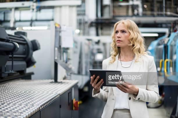 woman with tablet at machine in factory shop floor looking around - produktionsgerät stock-fotos und bilder