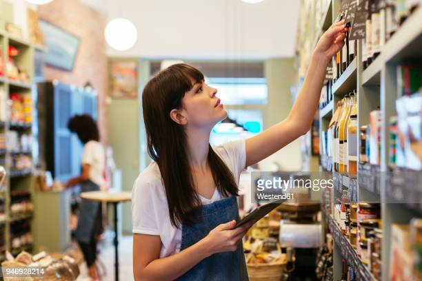 woman with tablet at shelf in a store - checklist stock pictures, royalty-free photos & images