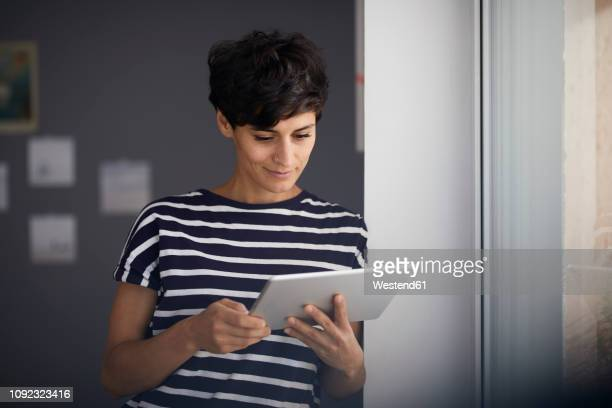 woman with tablet at the window - using digital tablet stock pictures, royalty-free photos & images
