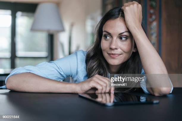 woman with tablet leaning on table - 30 34 anos imagens e fotografias de stock