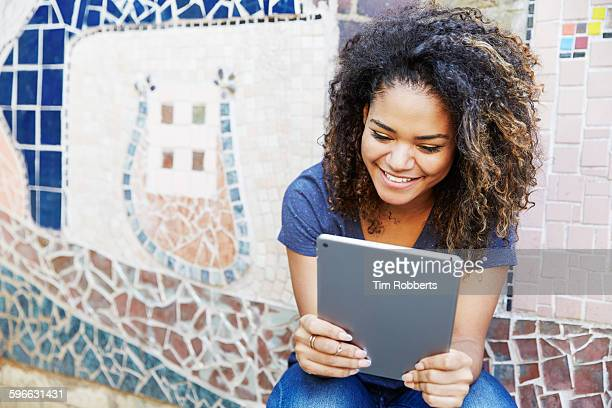 Woman with tablet, mosaic wall.