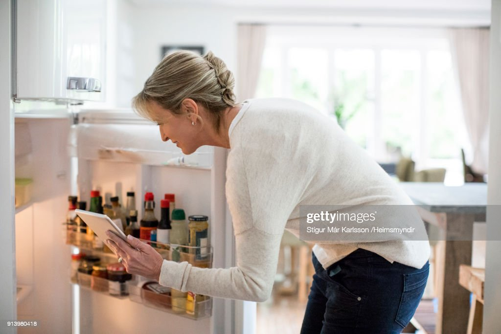 Woman with tablet PC looking into refrigerator : Stock Photo