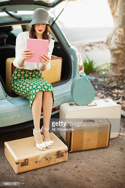 Woman with tablet sitting in the back of a car