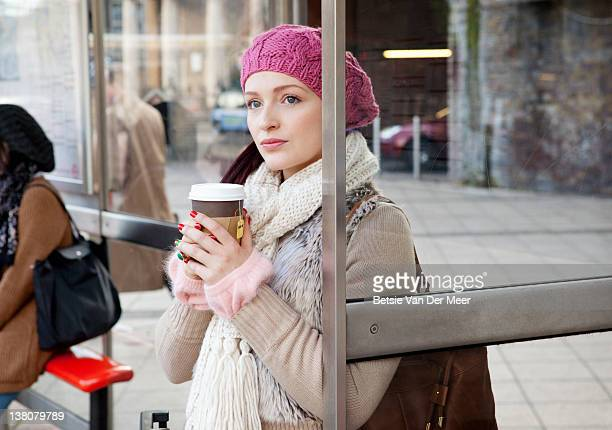 Woman with take away tea waiting for bus.