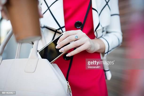Woman with takeaway coffee putting phone in handbag
