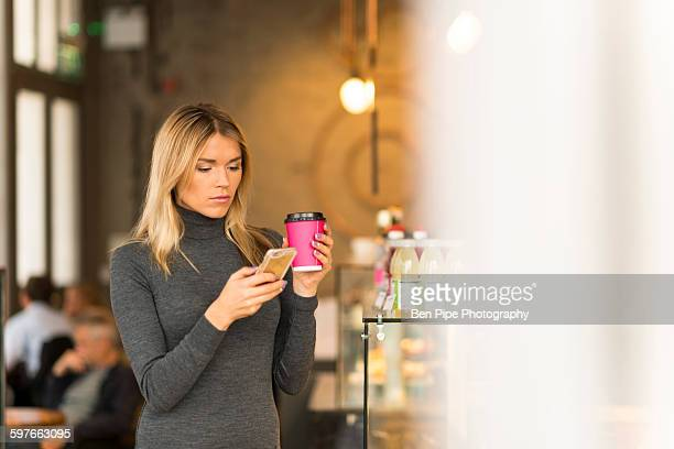 Woman with takeaway coffee using smartphone