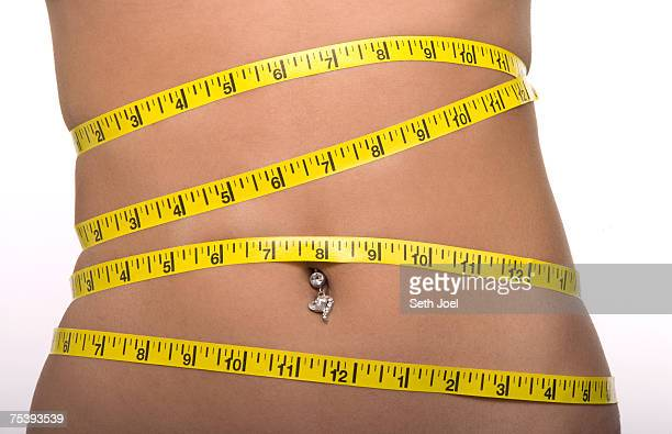 Woman with tape measure around abdomen with belly button piercing, mid section, close-up