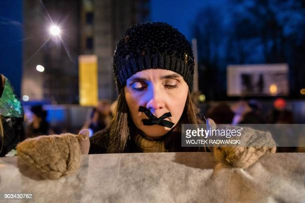 TOPSHOT A woman with tape on her mouth holds a banner during an antigovernment and proabortion demonstration on January 10 2018 outside the...