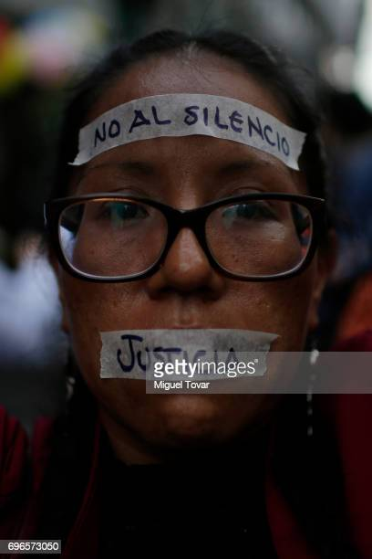A woman with tapes on her face that read 'No to silence' and 'Justice' looks on during a demonstration to end violence against journalists in Mexico...