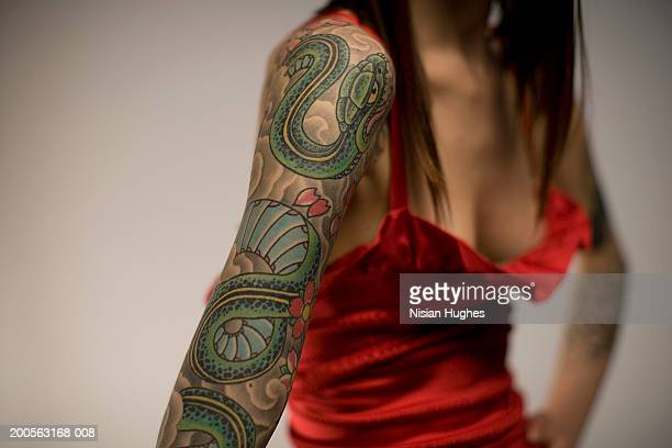 Woman with tattooed arm, mid section