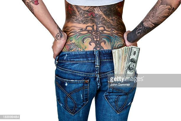 woman with tattooed back and cash in pocket - cash back in your pocket stock pictures, royalty-free photos & images