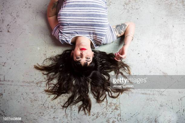 A woman with tattoos and red lipstick lies on a concrete floor