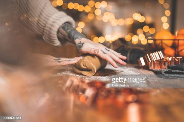 woman with tattoos baking gingerbread cookies at home - gingerbread cookie stock pictures, royalty-free photos & images
