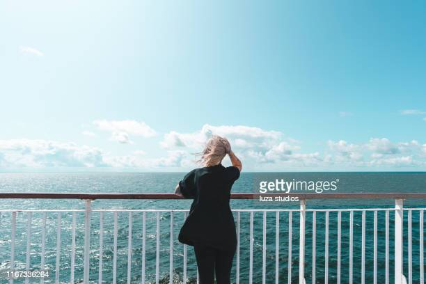 a woman with tattoos is traveling by ferry on her vacation - ferry stock pictures, royalty-free photos & images