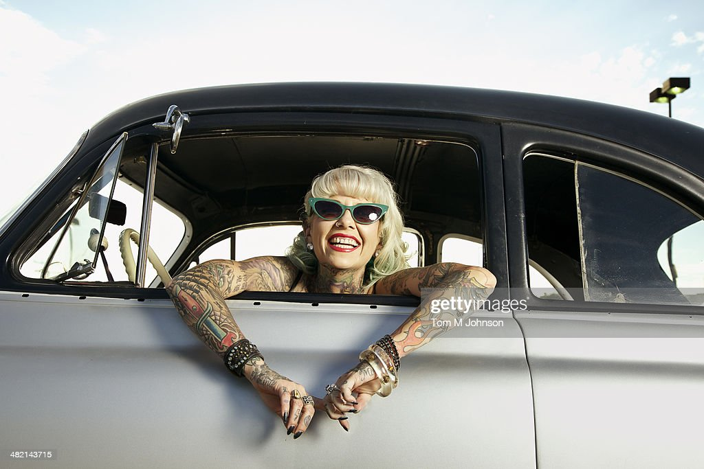Woman with tattoos leaning out window of 1951 Chevy : Stock Photo