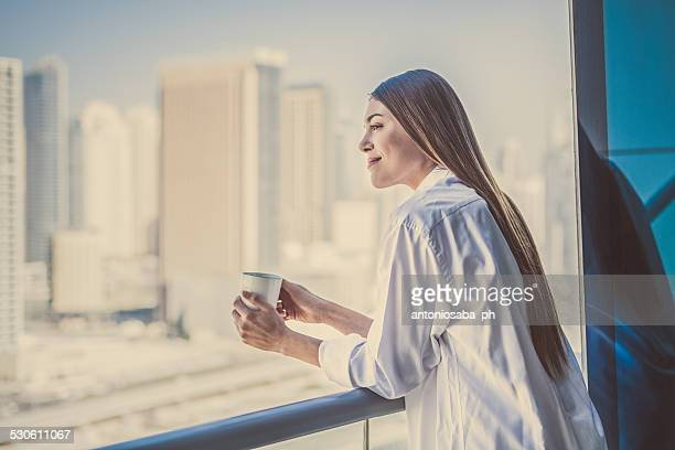woman with tea at the balcony.