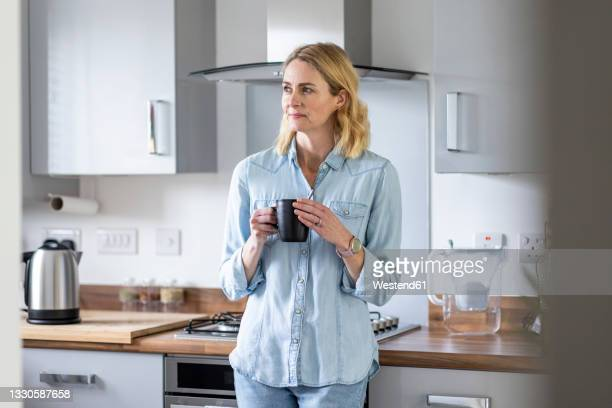 woman with tea cup looking away while standing in kitchen at home - mature women stock pictures, royalty-free photos & images