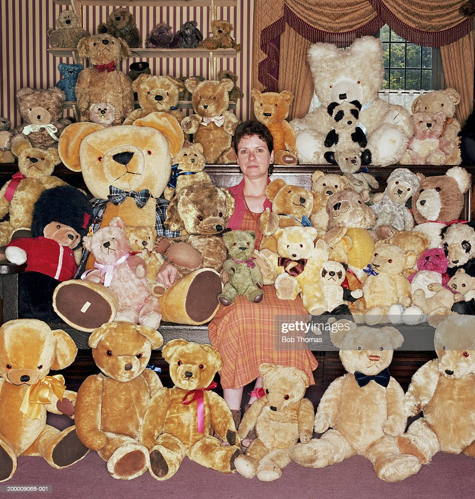 Woman with teddy bear collection, portrait : Photo