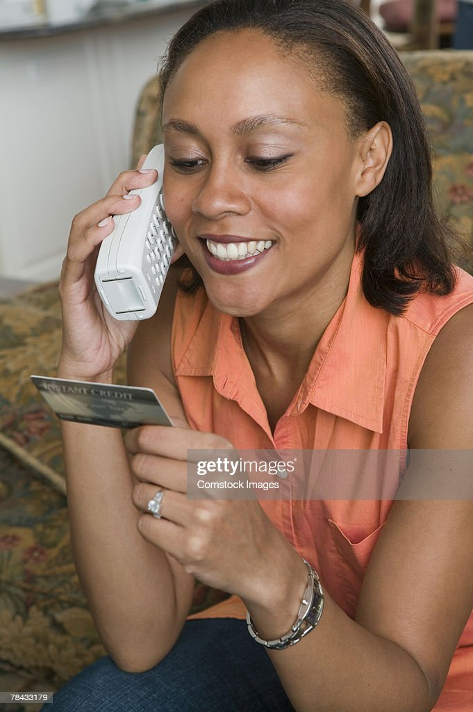 Woman with telephone and credit card : Stockfoto