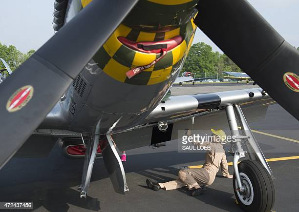 A woman with the Commemorative Air Force polishes a P51 Mustang airplane prior to a practice flight with dozens of World War II era aircraft near...