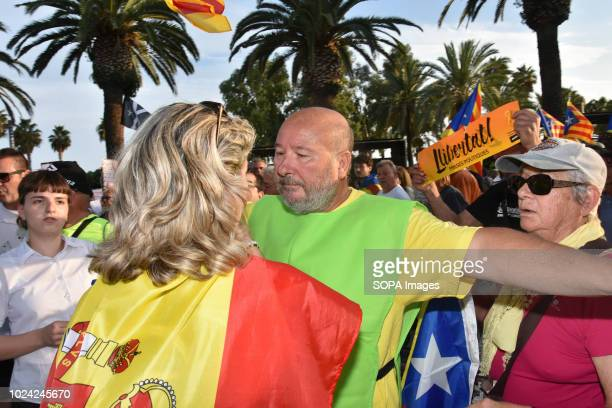 A woman with the flag of Spain rebukes at the head of the independence march and a member of the organization avoids passing the security cordon...