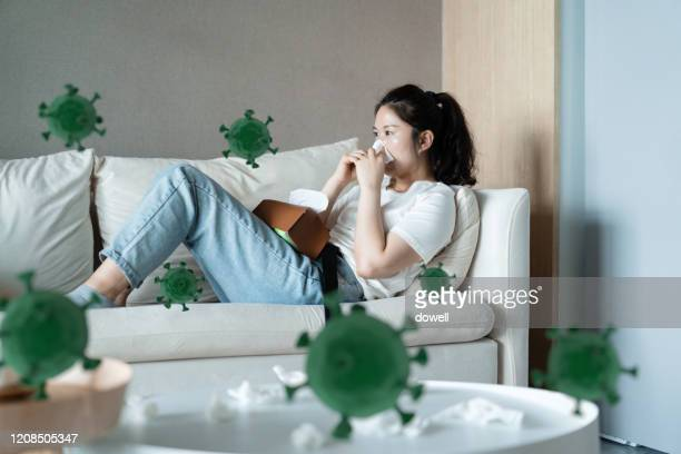 woman with the flu blowing her nose - infectious disease stock pictures, royalty-free photos & images