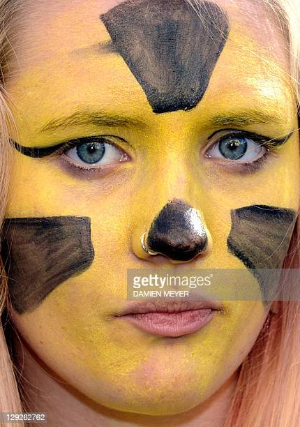 A woman with the nuclear logo painted on her face takes part in a demonstration by thousands of people to call for the closure of France's nuclear...