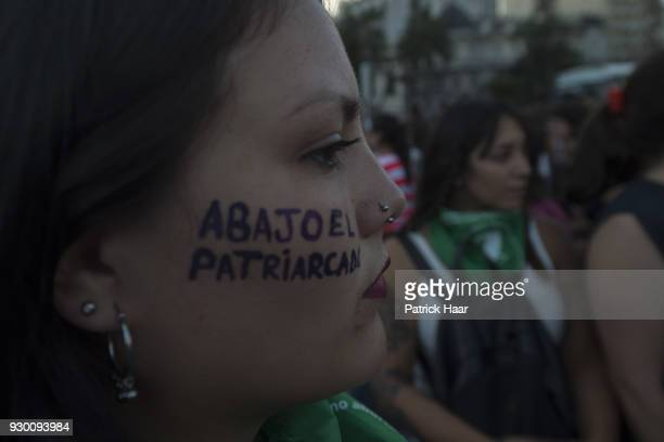 A woman with the phrase 'Down with patriarchy' written in her face takes part in a mass demonstration as part of International Women's Day strike in...