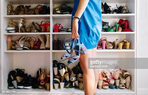 woman with the shoes in the hand and woman's shoes in the rack - neat stock pictures, royalty-free photos & images
