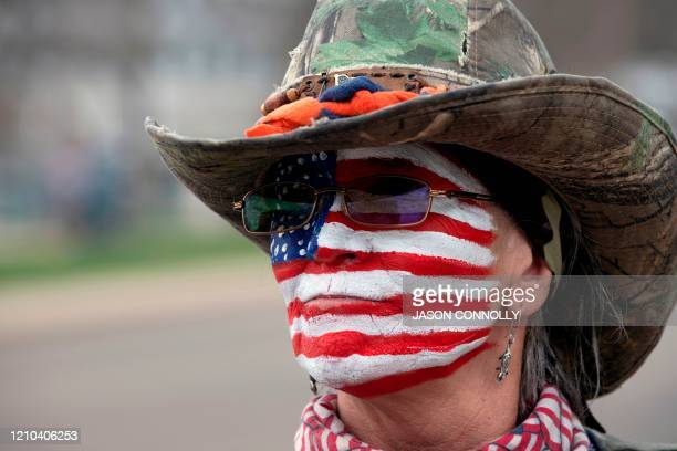 A woman with the US flag painted on her face gathers with others to protest coronavirus stayathome orders during a ReOpen Colorado rally in Denver...