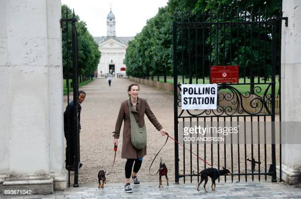 A woman with three dogs leaves the polling station at Burton Court pavilion in southwest London on June 8 as Britain holds a general election As...