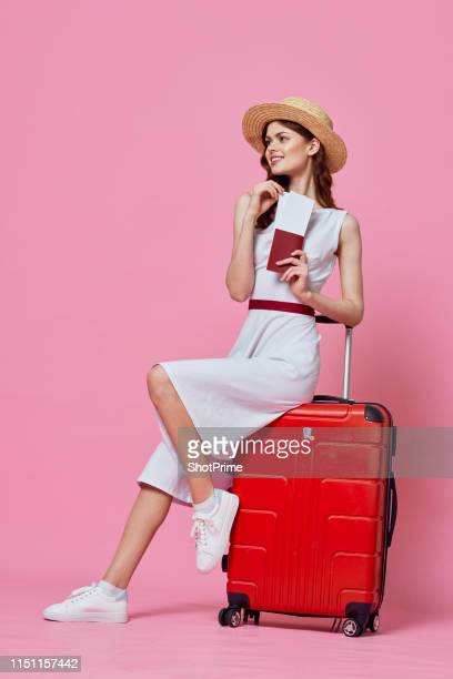 a woman with tickets in hand sits on a suitcase in a white dress and hat - passagier stock-fotos und bilder
