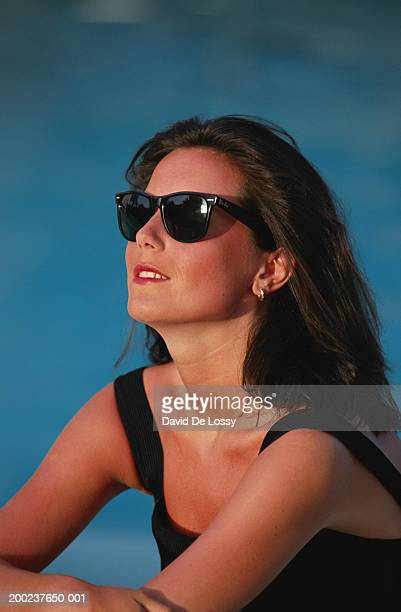 woman with tilting head at pool side - capelli neri foto e immagini stock