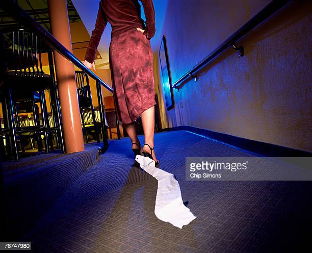 woman with toilet paper stuck to shoe - funny toilet paper foto e immagini stock
