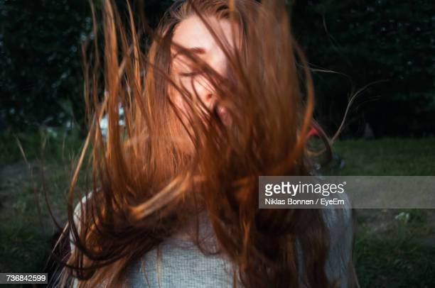 Woman With Tousled Brown Hair In Yard At Night