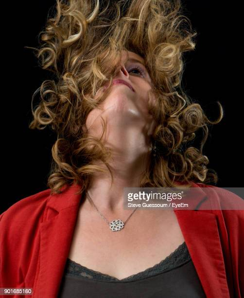 Woman With Tousled Hair Against Black Background
