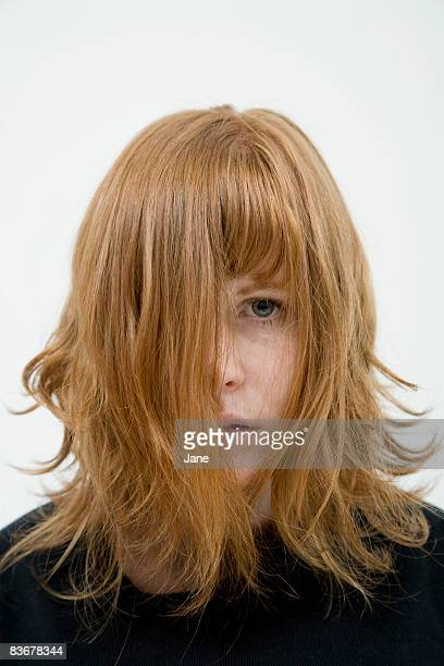 a woman with tousled hair hanging in her face - corte de pelo por encima de los hombros fotografías e imágenes de stock